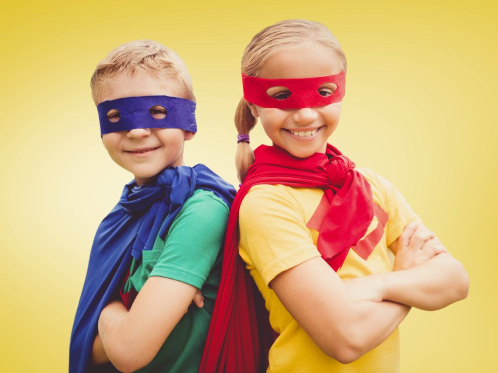 Portrait of kids in superhero costumes against yellow background