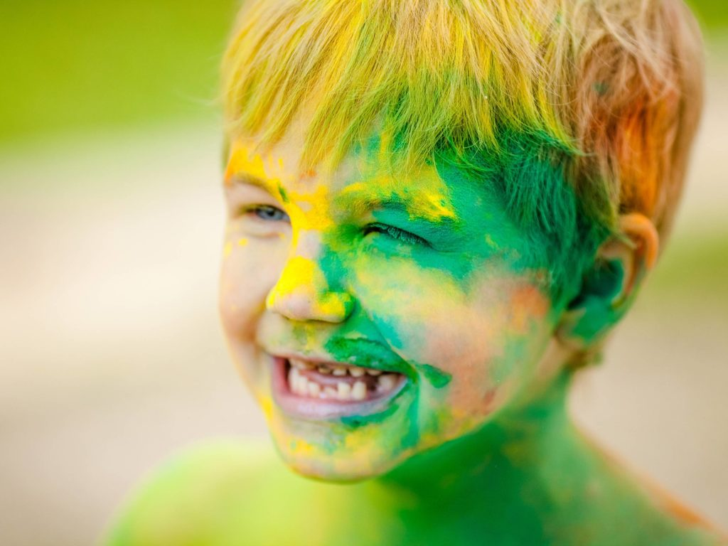 Portrait of happy boy with blue eyes with strabismus smeared with colored powder.
